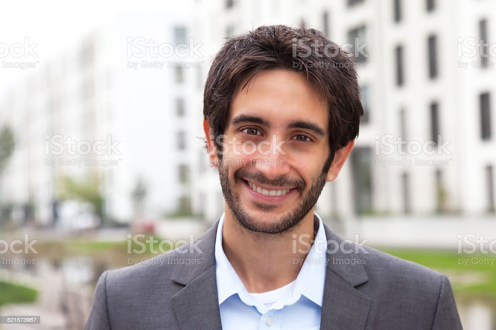 Happy businessman with black hair and beard in the city stock photo