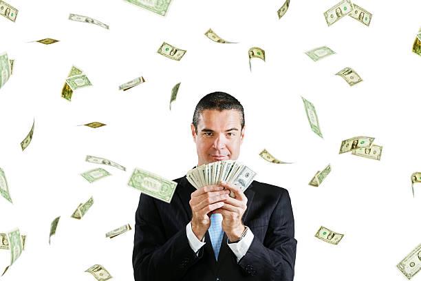glücklich geschäftsmann mit handvoll dollar plus more raining down - sterntaler stock-fotos und bilder