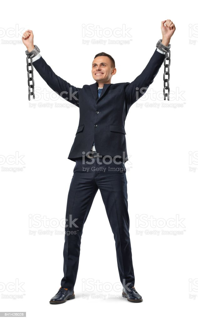 A happy businessman with hands raised up showing broken shackles on white background stock photo