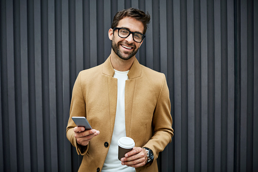 Happy businessman with disposable cup and smart phone. Portrait of professional wearing smart casuals. He is standing against wall.