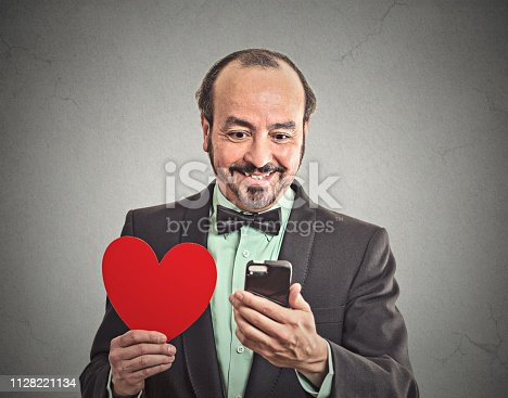 istock Happy businessman with smartphone and red heart 1128221134