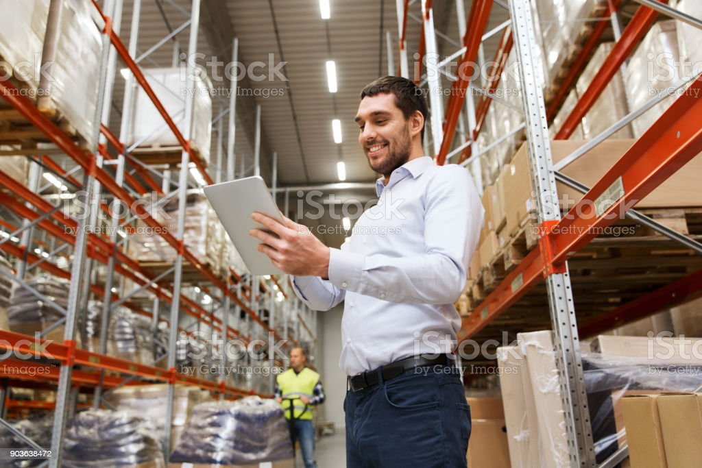 happy businessman with tablet pc at warehouse stock photo