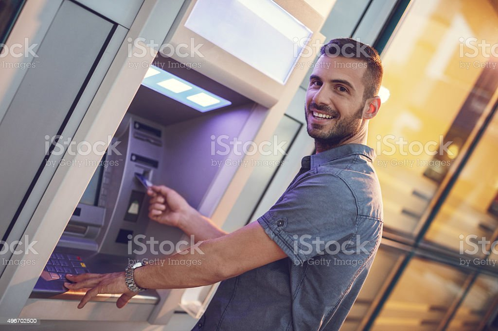 Happy businessman withdrawing money from a cash machine. stock photo
