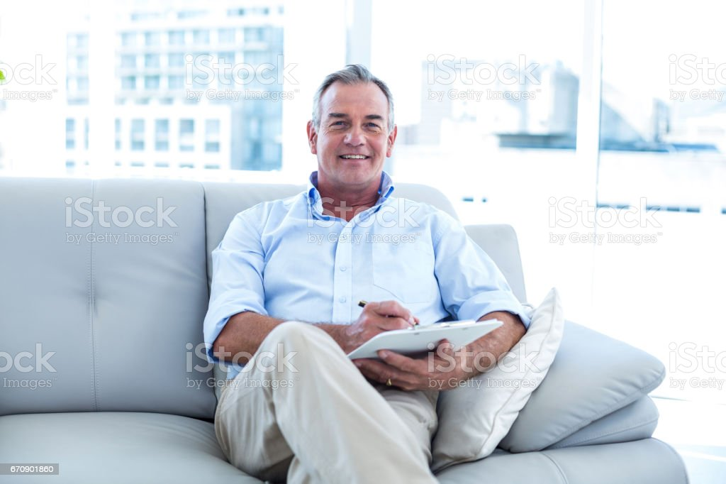 Happy businessman writing on notepad stock photo