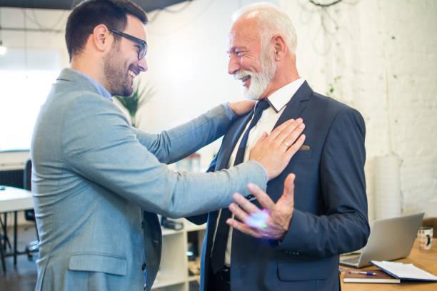 Glückliche Geschäftsleute grüßen sich im Büro. Mitarbeiter mittleren Alters, gratuliert seinem Mentor. – Foto