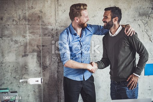 Young happy businessmen talking while shaking hands in the office.