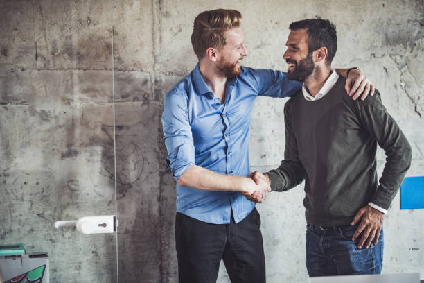 Happy businessmen greeting each other in the office. Young happy businessmen talking while shaking hands in the office. two people stock pictures, royalty-free photos & images