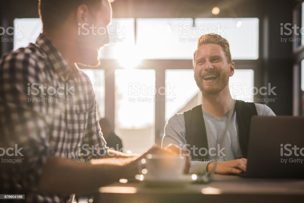 Two happy businessmen using laptops in a cafe and talking to each...