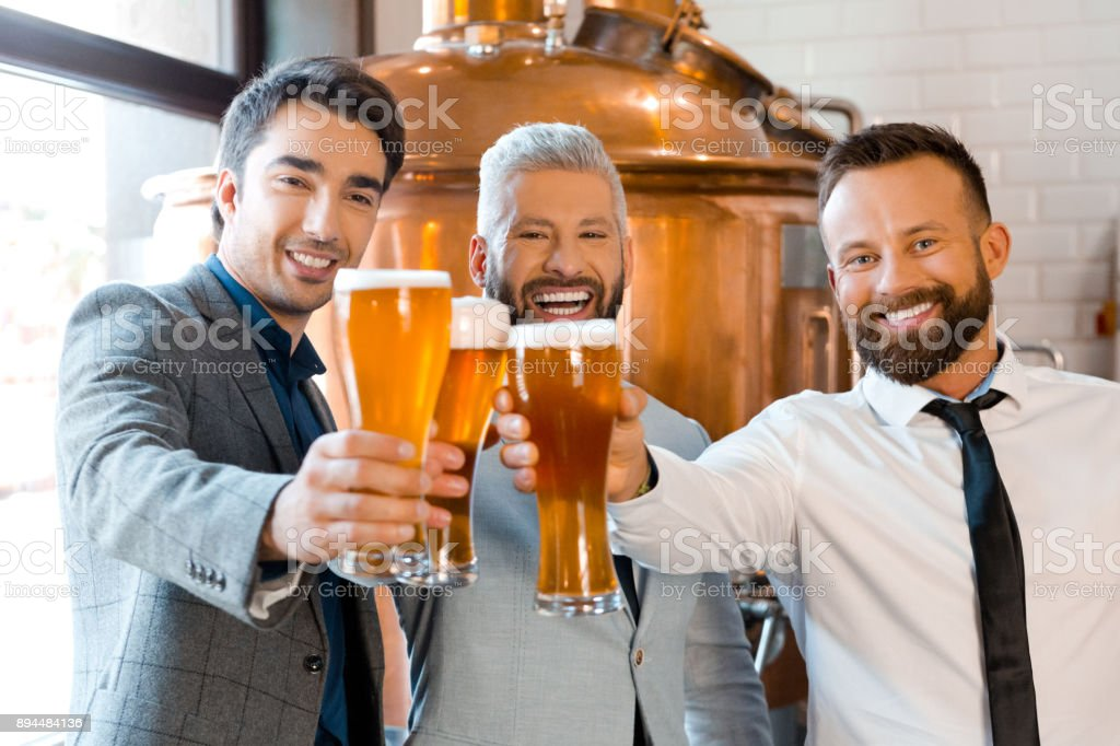 Happy businessmen toasting beer in brewery Portrait of happy businessmen toasting beer in brewery. Businesspeople celebrating success with beers at micro brewery. Adult Stock Photo