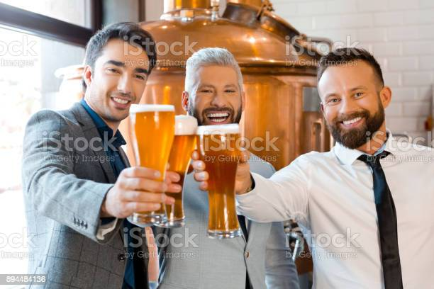Happy Businessmen Toasting Beer In Brewery Stock Photo - Download Image Now