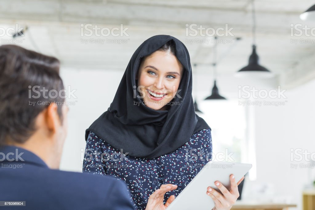 Happy businesspeople discussing work Muslim businesswoman holding digital tablet and talking with male colleague in office. Happy businesspeople discussing work. 20-29 Years Stock Photo
