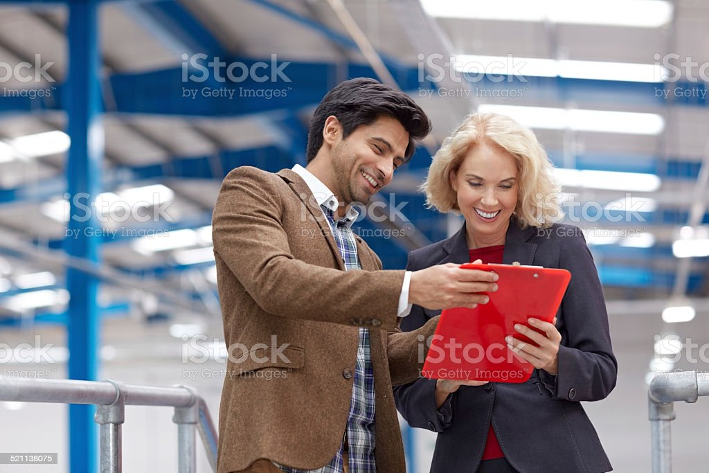 Happy businesspeople in factory with clipboard stock photo