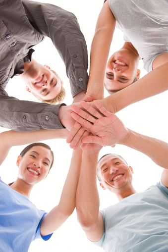 514325215 istock photo Happy businesspeople placing their hands top of each other 483486570