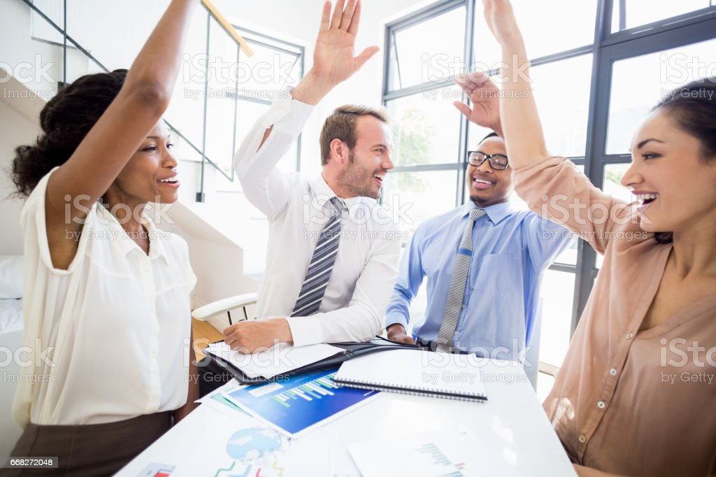 Happy businesspeople raising their hands during a meeting foto stock royalty-free