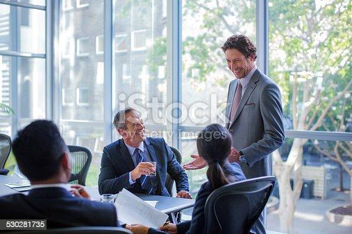 Happy businessman talking to colleagues in board room at office