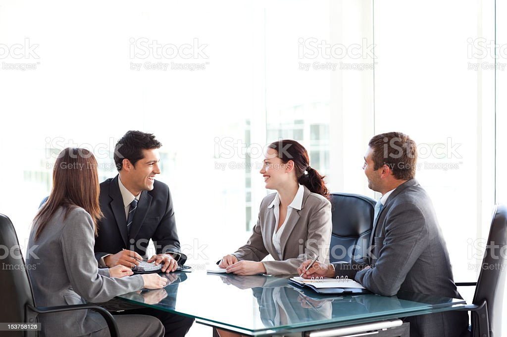 Happy businessteam talking together during a meeting stock photo