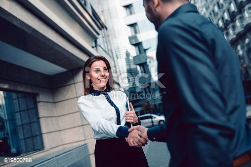 Two young business colleagues are having handshake with smiling faces for success and agreement, outdoor in front of the office building. Welcoming a job applicant.