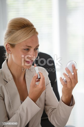 Portrait of smiling mid adult businesswoman sitting at the office and looking at the hand mirror while applying lipstick.