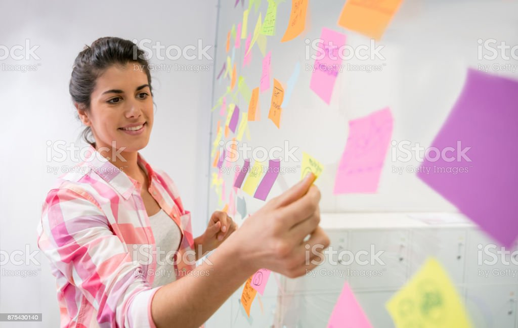 Happy businesswoman brainstorming ideas and sticking adhesive notes...