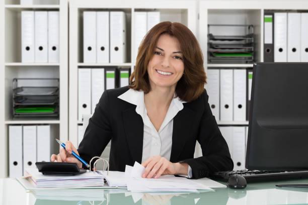 heureuse femme d'affaires de calculer les taxes - directrice photos et images de collection