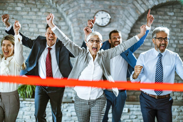 Happy businesswoman crossing finish line during sports race in the office. Cheerful senior businesswoman celebrating her success while crossing the finish line in the office. win stock pictures, royalty-free photos & images