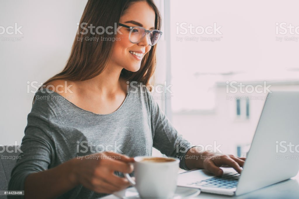 Happy businesswoman drinking coffee at laptop stock photo