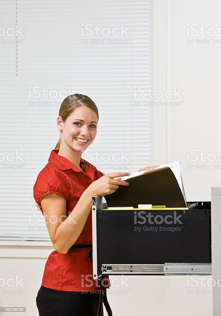 Happy businesswoman filing papers in file cabinet royalty-free stock photo