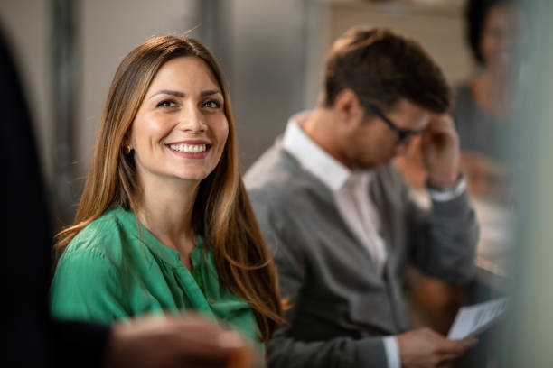 Happy businesswoman having a meeting with colleagues in the office. Young smiling businesswoman attending a training class  with her coworkers in board room. attending stock pictures, royalty-free photos & images
