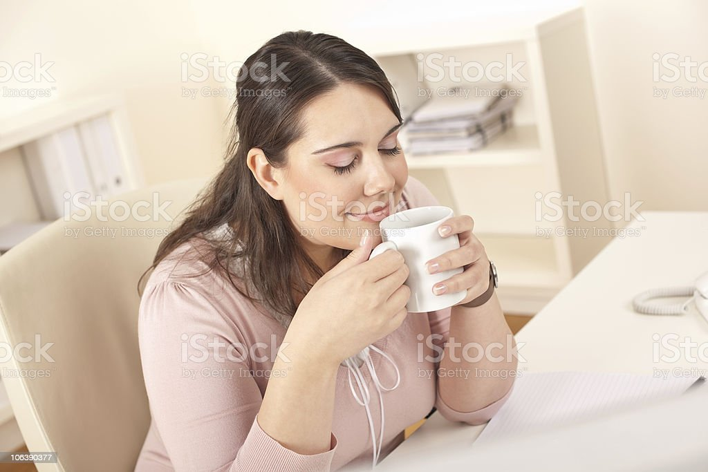 Happy businesswoman having coffee break at office royalty-free stock photo
