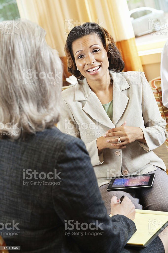 Happy businesswoman having work discussion with experienced colleague royalty-free stock photo