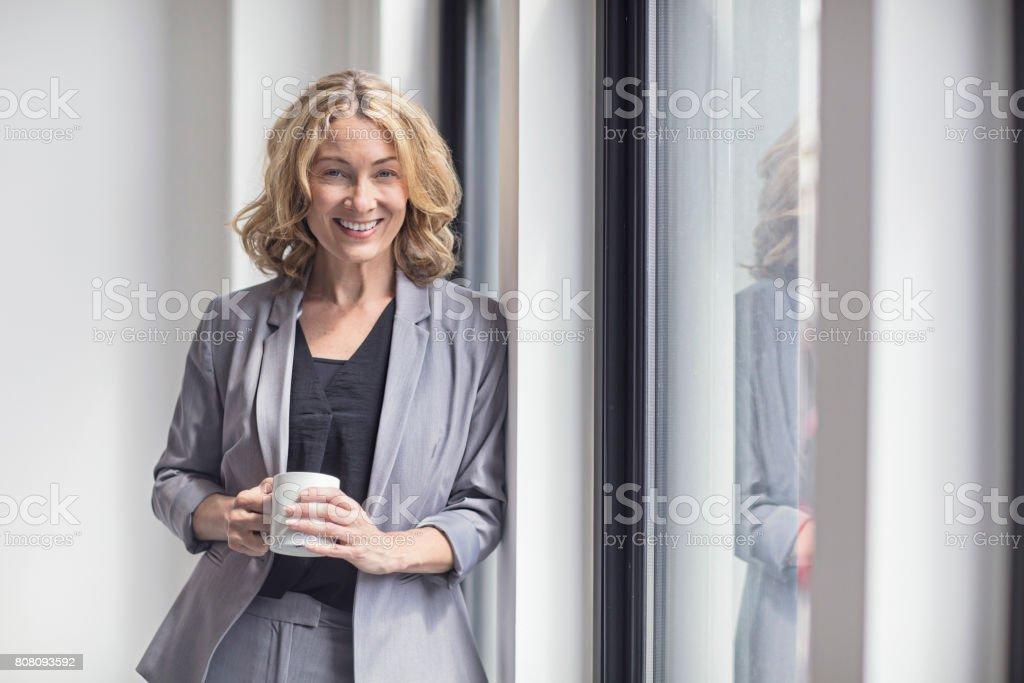 Happy businesswoman holding coffee mug by window stock photo