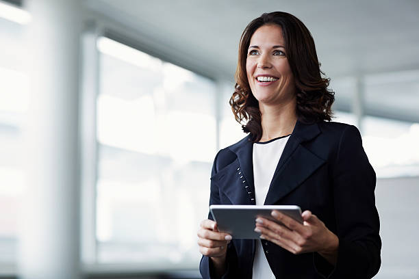 happy businesswoman holding digital tablet - wegsehen stock-fotos und bilder