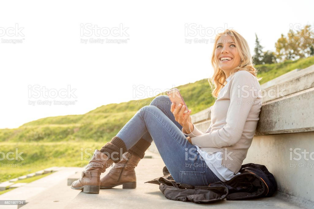 Happy businesswoman holding mobile phone outdoors stock photo