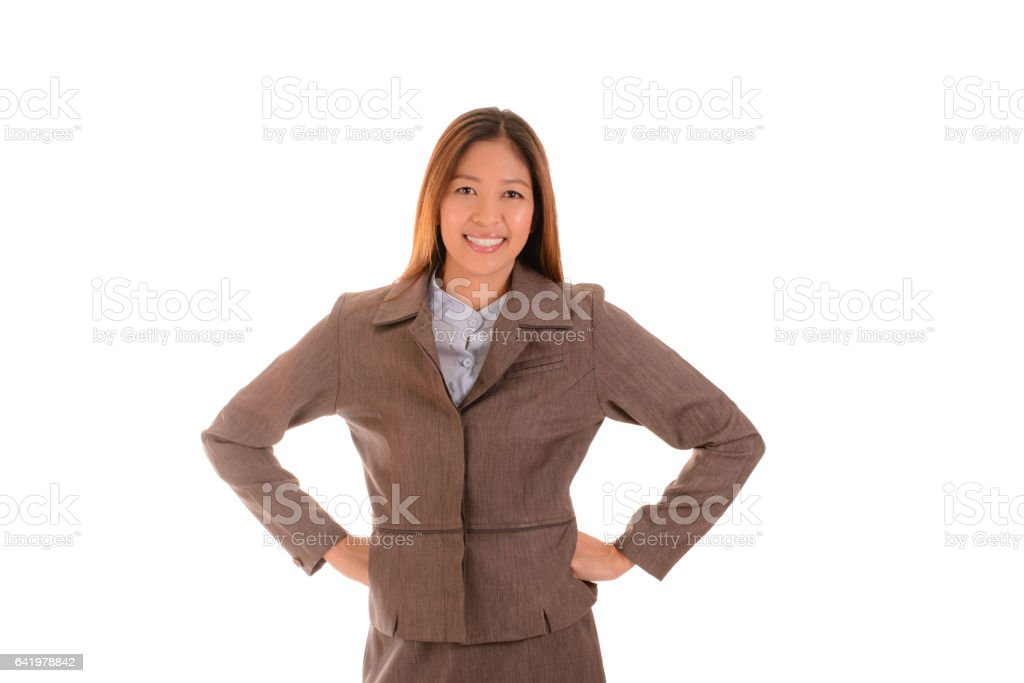 Happy businesswoman in brown suit is smiling and arms akimbo on white background. stock photo