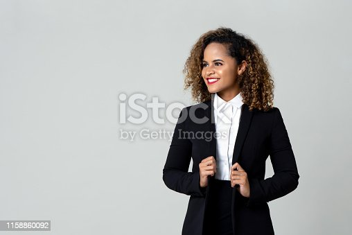Cheerful African American business woman in black suit with curly hair looking away isolated against gray background