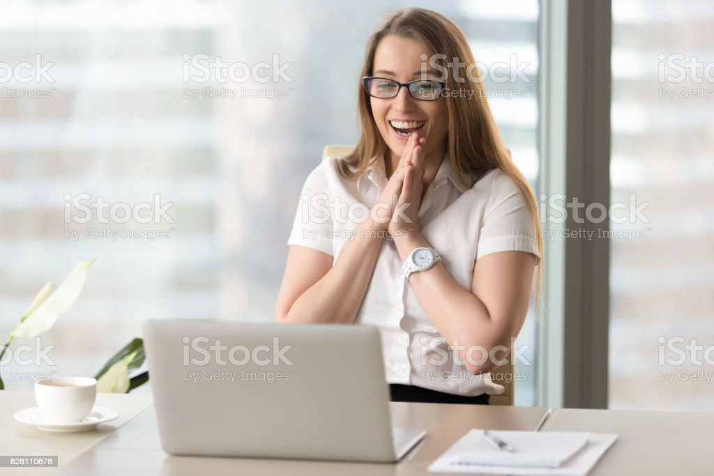 Happy businesswoman laughing with joy, gladly looking at laptop screen – zdjęcie