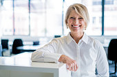 A photo of happy businesswoman leaning on cubicle in office. Portrait of smiling female professional in formals. Executive is at brightly lit workplace.