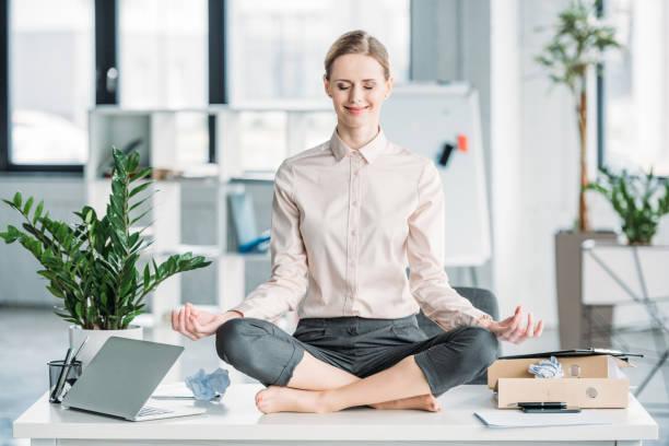glücklich geschäftsfrau meditieren im lotussitz auf unordentlich tisch im büro - yoga fürs büro stock-fotos und bilder