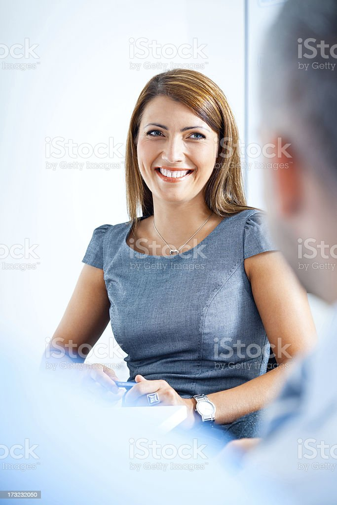Happy businesswoman Focus on the happy businesswoman smiling to her business colleagues during business meeting. Achievement Stock Photo