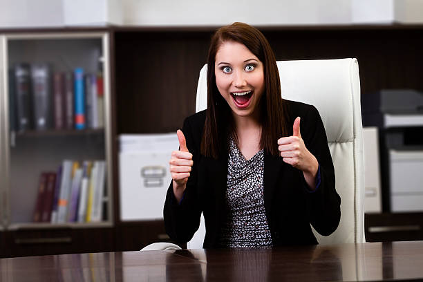 Happy businesswoman showing thumbs up sign stock photo