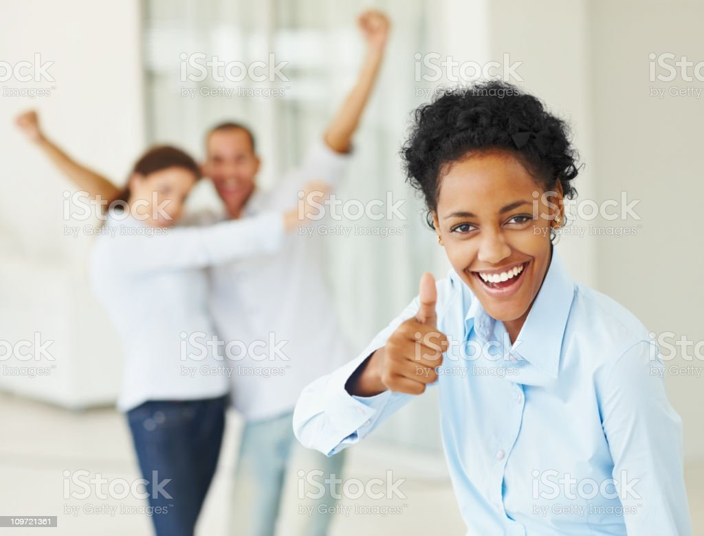 Happy businesswoman showing thumbs up sign with colleagues in background royalty-free stock photo