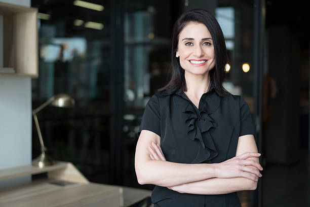 happy businesswoman standing arms crossed - 30 39 jaar stockfoto's en -beelden