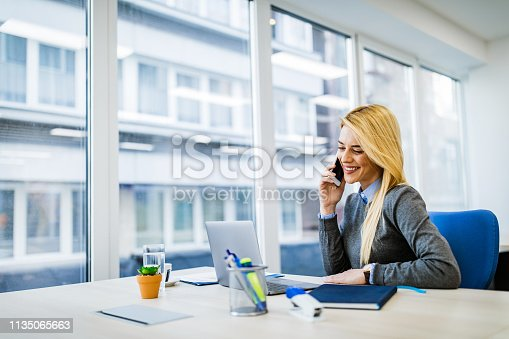 istock Happy businesswoman talking on cell phone while working on laptop in the office. 1135065663
