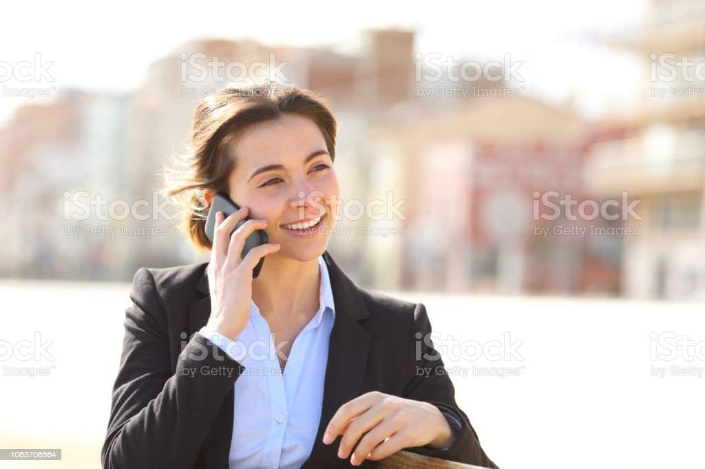Happy Businesswoman Talking On Phone In A Park Stock Photo