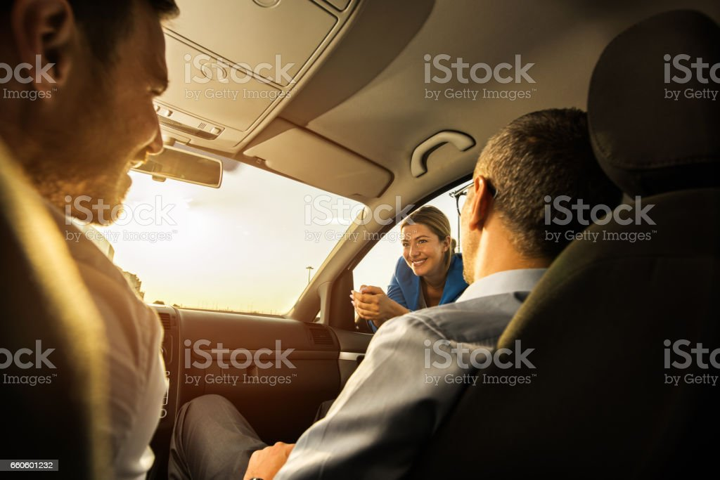 Happy businesswoman talking to her colleagues inside of the car. royalty-free stock photo