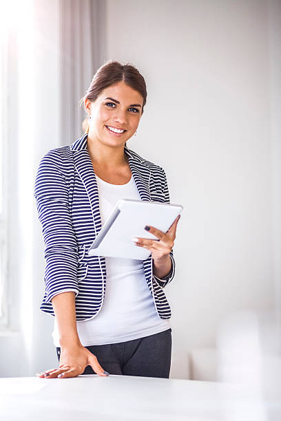 Happy businesswoman using digital tablet by desk at office – Foto