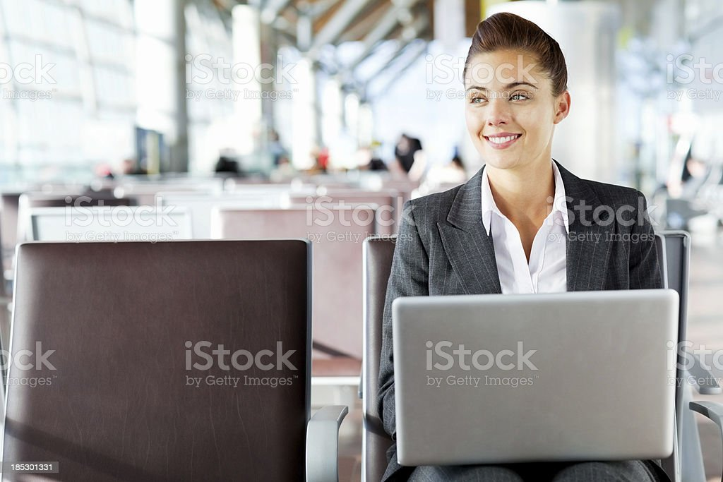 Happy Businesswoman Using Laptop At Airport royalty-free stock photo