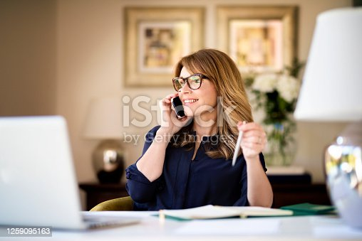 Shot happy businesswoman sitting at desk behind her laptop and talking with somebody on her mobile phone while working from home. Home office.