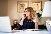 istock Happy businesswoman using mobile and laptop while working at home 1259095163