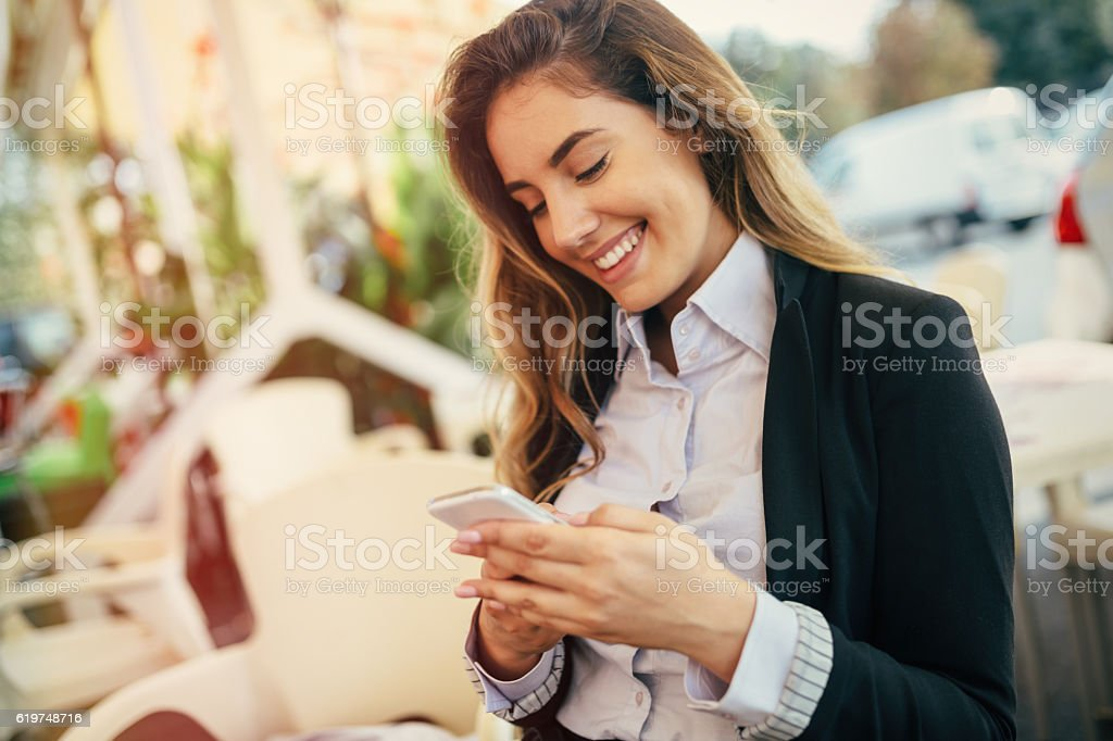 Happy businesswoman using phone stock photo